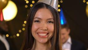Szczęśliwy azjatykci kobiety dmuchanie na confetti i robić lotniczemu buziakowi przy przyjęciem, świętowanie zbiory