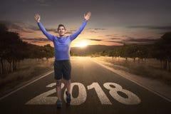Szczęśliwy azjatykci mężczyzna zasięg koniec z 2018 liczbami na ulicie obraz stock