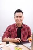 Szczęśliwy azjatykci męski projektant grafik komputerowych mienia koloru fan w jego ręce Zdjęcie Royalty Free