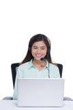 Szczęśliwy azjatykci młodej kobiety obsiadanie, działanie z laptopem i używać słuchawki w biurze Obrazy Royalty Free