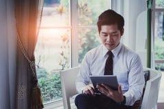 Szczęśliwy azjatykci młody przystojny biznesmen używa pastylkę Obraz Royalty Free
