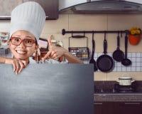 Szczęśliwy azjatykci szef kuchni pokazuje menu znaka na chalkboard Obrazy Stock