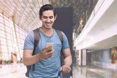 Szczęśliwy azjatykci turystyczny mienie telefon, walizka i Obrazy Stock