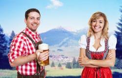 Szczęśliwy bavarian mężczyzna z piwnym kubkiem i piękną blondynki kobietą z Zdjęcie Royalty Free
