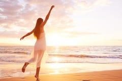 Szczęśliwy Beztroski kobieta taniec na plaży przy zmierzchem Zdjęcie Royalty Free