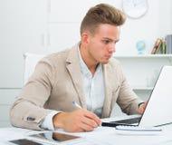 Szczęśliwy biurowy męski pracownik przy miejscem pracy Obraz Stock
