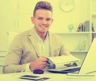 Szczęśliwy biurowy męski pracownik przy miejscem pracy Fotografia Stock