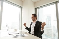 Szczęśliwy biznesmen świętuje imponująco achi przed laptopem Zdjęcia Stock