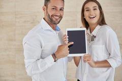 Szczęśliwy biznesmen i bizneswoman trzyma brandnew pastylkę Zdjęcia Stock