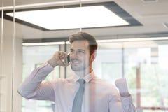 Szczęśliwy biznesmen opowiada na smartphone widzieć przez okno przy biurem fotografia royalty free