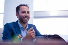 Szczęśliwy biznesmen patrzeje oddalony podczas gdy siedzący w biurze Obraz Stock
