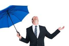 Szczęśliwy biznesmen trzyma błękitnego parasol i przyglądającego up Fotografia Royalty Free