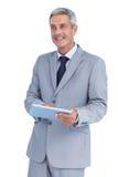 Szczęśliwy biznesmen używa pastylka komputer osobistego patrzeje daleko od Obraz Royalty Free
