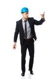 Szczęśliwy biznesmen w hełmie wskazuje jego palec up fotografia stock