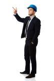 Szczęśliwy biznesmen w hełmie wskazuje jego palec up obrazy stock