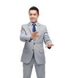 Szczęśliwy biznesmen w kostiumu macaniu coś Zdjęcia Royalty Free