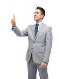 Szczęśliwy biznesmen w kostiumu macaniu coś Zdjęcie Stock