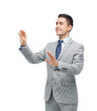Szczęśliwy biznesmen w kostiumu macaniu coś Obraz Royalty Free