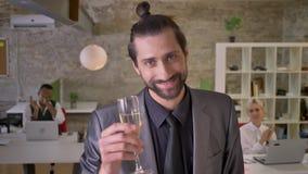 Szczęśliwy biznesmen z brodą jest stojący i trzymający szkło szampan w biurze, koledzy klasczą, firma zbiory