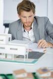 Szczęśliwy biznesmen z domu modelem biurkiem Obrazy Stock