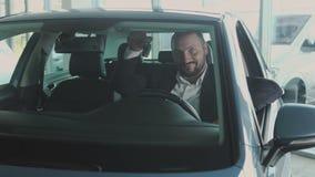 Szczęśliwy biznesmen z kluczami wśrodku jego nowego samochodu w przedstawicielstwie firmy samochodowej zdjęcie wideo