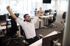 Szczęśliwy biznesmen z rękami podnosić w biurze Obraz Royalty Free