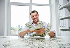 Szczęśliwy biznesmen z rozsypiskiem pieniądze w biurze Fotografia Stock