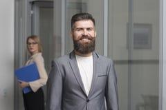Szczęśliwy biznesmen z zamazaną kobietą na tle Brodaty mężczyzna w formalnym kostiumu w biurze Ufny mężczyzna uśmiech z brodą obraz stock
