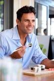 Szczęśliwy biznesmena łasowania suszi przy restauracją Fotografia Royalty Free