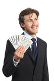 Szczęśliwy biznesmena mienia pieniądze i patrzeć z ukosa Zdjęcia Stock