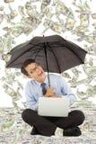 Szczęśliwy biznesowego mężczyzna obsiadanie na podłoga z dolara amerykańskiego deszczem Fotografia Royalty Free