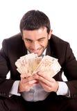 Szczęśliwy biznesowego mężczyzna obsiadanie na prosiątko banka pieniądze odliczających euro Fotografia Royalty Free