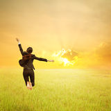 Szczęśliwy biznesowej kobiety doskakiwanie w zielonym ryżu polu, zmierzchu i Zdjęcie Stock