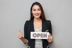 Szczęśliwy biznesowej kobiety mienia nameplate otwarty i seansu kciuk up obraz royalty free
