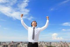 Szczęśliwy biznesowy mężczyzna powstaje ręki z pejzażem miejskim zdjęcie royalty free