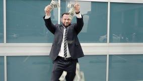 Szczęśliwy biznesowy mężczyzna rzuca dolary w ulicie zbiory