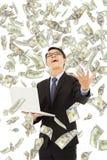 Szczęśliwy biznesowy mężczyzna trzyma laptop z pieniądze deszczem Zdjęcia Stock