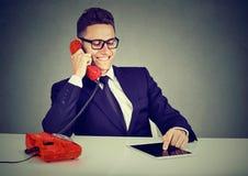 Szczęśliwy biznesowy mężczyzna używa pastylka komputer ma rozmowę na telefonie obrazy stock