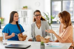 Szczęśliwy bizneswomanów jeść bierze out jedzenie przy biurem Obrazy Royalty Free