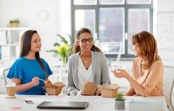 Szczęśliwy bizneswomanów jeść bierze out jedzenie przy biurem Fotografia Royalty Free