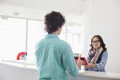 Szczęśliwy bizneswoman daje kartotekom męski kolega przy kontuarem w kreatywnie biurze Zdjęcie Royalty Free