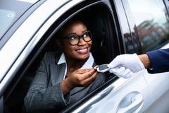 Szcz??liwy bizneswoman Daje samochodu kluczowi lokaj obraz royalty free