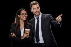 Szczęśliwy bizneswoman pije kawę w formalnej odzieży, podczas gdy biznesmen wskazuje gdzieś Fotografia Royalty Free