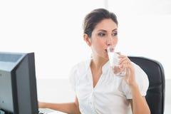 Szczęśliwy bizneswoman pije szkło woda przy jej biurkiem Zdjęcia Stock