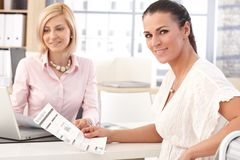 Szczęśliwy bizneswoman przy biurem z biznesowym raportem zdjęcia stock