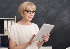 Szczęśliwy bizneswoman przy pracą używać cyfrową pastylkę Zdjęcia Royalty Free