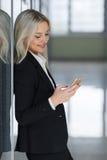 Szczęśliwy bizneswoman uśmiecha się smartphone i używa w biurze Obrazy Royalty Free