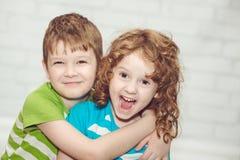 Szczęśliwy brat, siostrzany ono uśmiecha się i obejmować. Fotografia Stock