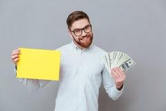 Szczęśliwy brodaty biznesmena mienia copyspace puste miejsce i pieniądze Zdjęcia Stock