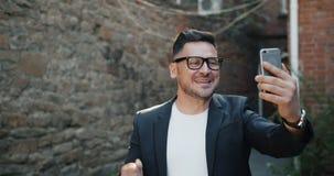 Szczęśliwy brodaty facet robi onlinemu wideo wezwania mienia smartphone opowiada outdoors zdjęcie wideo